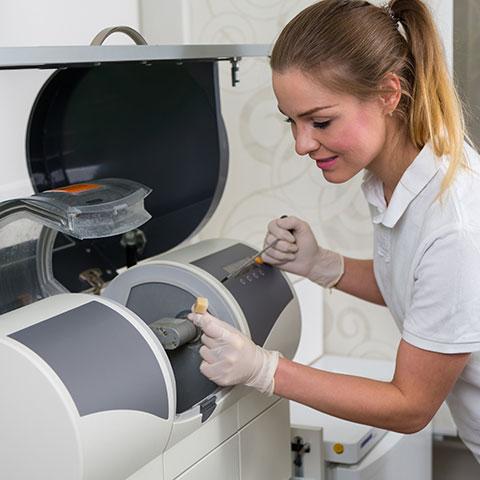 A dental assistant prepping the CEREC machine