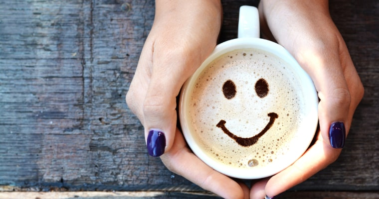 female holding a cup of coffee with smiley face, and coffee can lower cancer risk.