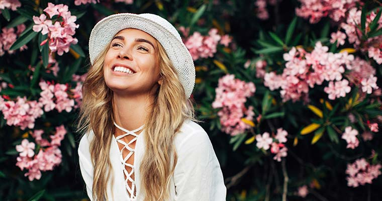 Young blond girl smiling wearing white hat and shirt against flower background, showing off beautiful professional teeth whitening results